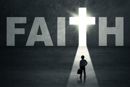 jesus standing: Little kid standing in front of faith door with bright light Stock Photo