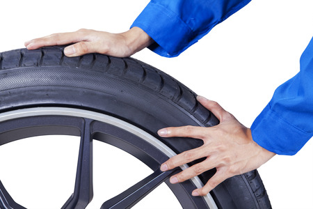 disassembly: Closeup of mechanic hands pushing a black tire in studio, isolated on white background Stock Photo