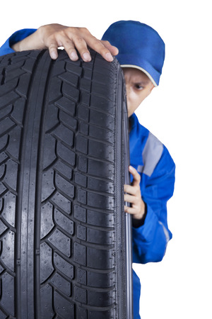 tire repair shop: Male technician expert checking a tire texture while wearing a blue uniform, isolated on white Stock Photo
