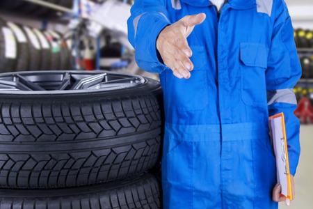 Man monteur met blauwe uniform staande in de werkplaats en biedt handdruk