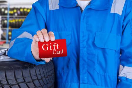 dar un regalo: Persona mec�nico permanente en el taller mientras que muestra una tarjeta de regalo Foto de archivo