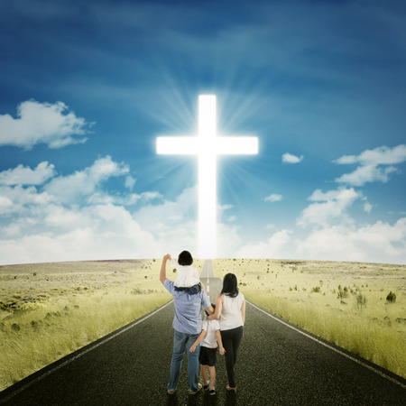 jesus clouds: Back view of two parents standing on the road with their children looking at a cross