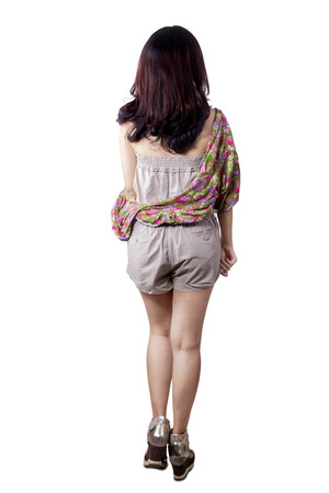 short back: Backside view of young girl with casual clothes walking forward, isolated over white background