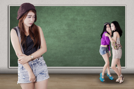 rejection sad: Portrait of lonely teenage girl standing in the class while mocked by her friends