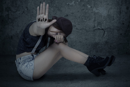 lonely person: Lonely teenage girl sitting on the floor with a wall background, showing hand with a help text