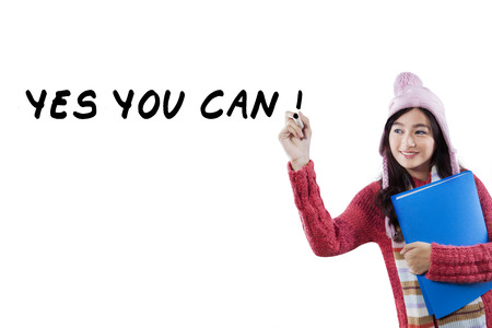Portrait of pretty girl wearing winter wear and hat, holding a folder and write advice words on whiteboard photo