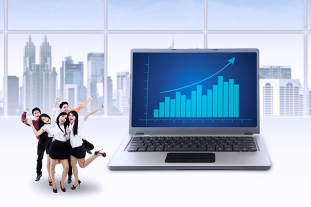Cheerful businesteam celebrate their achievement with business chart on laptop screen photo