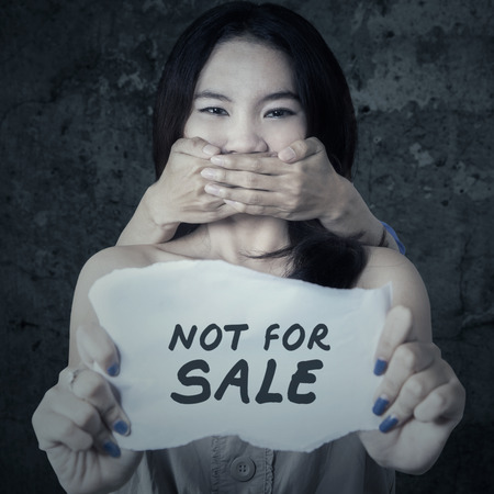 human trafficking: Portrait of adolescent girl holding a paper with a text of Not For Sale while her mouth covered by someone