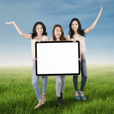 cute teen girl: Portrait of cheerful female students standing on the meadow while holding empty board