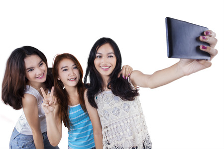 are taking: Group of happy teenage girls having fun and taking self picture together in the studio Stock Photo