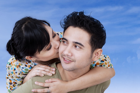 Portrait of young asian woman kissing her boyfriend under blue sky photo