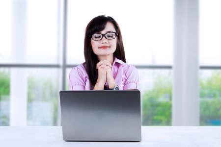 mujer orando: Empresaria joven con las manos juntas orando mientras estaba sentado en el escritorio en la oficina