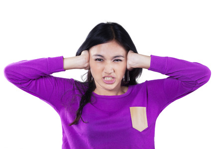 personas enojadas: Mujer estudiante de secundaria cerrar sus oídos con la expresión enojada, aislado sobre fondo blanco