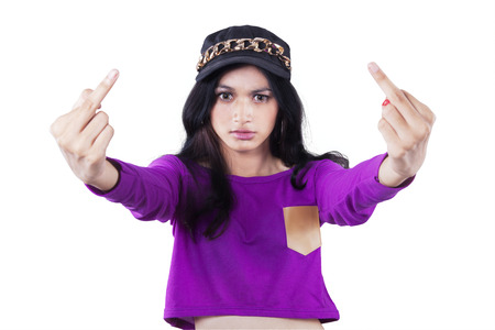 Portrait of teenage girl with casual clothes, showing two middle fingers with angry expression Stock Photo