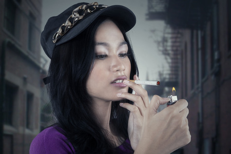 woman street: Portrait of teenage girl lighting up a cigarette with a match on the street