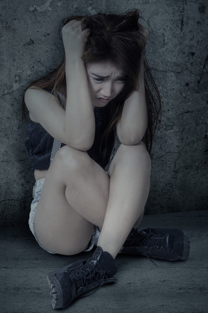 alone in the dark: Teenage girl sitting alone and looks depressed, shot against a dark background