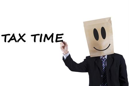 przypominać: Mężczyzna przedsiębiorca z głowy tektury pisze na tablicy podatku czasu przypomnieć czas płacenia podatku Zdjęcie Seryjne