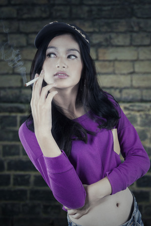 asian girl face: Portrait of casual teenage girl standing outdoors while smoking a cigarette Stock Photo