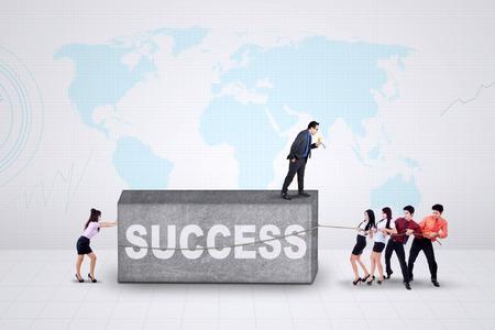 jovenes empresarios: Equipo de jóvenes empresarios tratan de mover una piedra con un texto de éxito