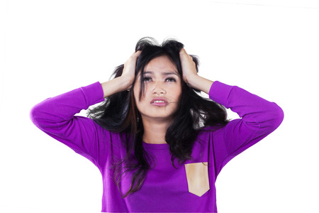 hair problem: Closeup of stressed teenage girl with casual clothes holding her head, isolated on white