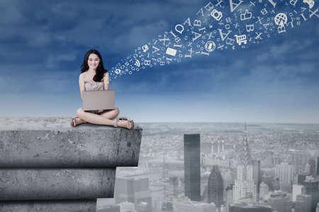 fille indienne: Adolescente assis sur le toit du b�timent tout en utilisant un ordinateur portable pour envoyer un message ou de l'information