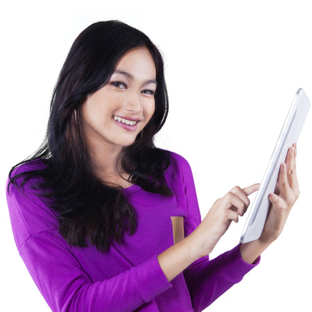 Attractive teenage girl with long hair, smiling at the camera while using a digital tablet in the studio photo