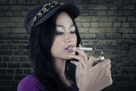 Portrait of a beautiful bad girl lighting up a cigarette with a match photo