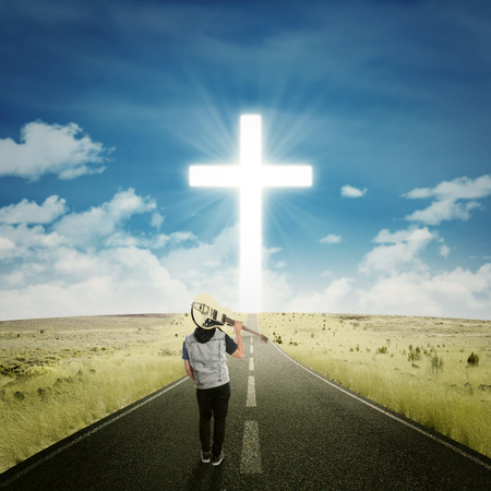 rock singer: Back view of male musician carrying a guitar and walk on the road to the cross
