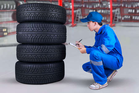car shop: Young male mechanic working in the workshop and inspecting the tires texture