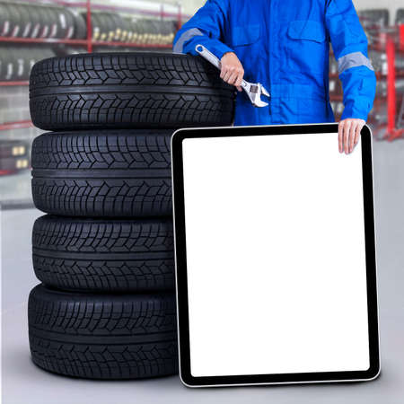 Male mechanic standing in the workshop while holding an empty board and lean on tires photo