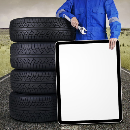 Male mechanic standing on the road while holding a blank placard and lean on tires photo