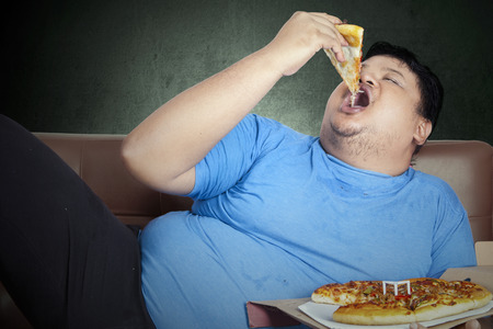 Zwaarlijvige persoon eet pizza zittend op de bank thuis Stockfoto