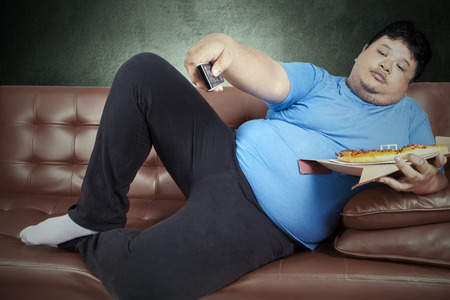Overweight man eats pizza while sitting on couch at home
