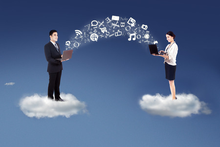 Two businesspeople standing on cloud and share information with laptop computer photo