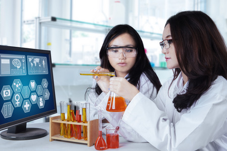 Portrait of two female science students working with chemical fluid in the lab