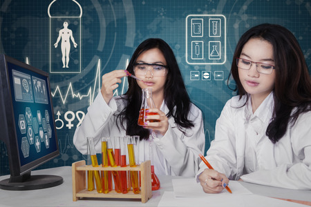 Two young students as a team doing experiment together in the modern laboratory photo