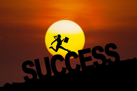 Silhouette of happy businesswoman celebrate her success by jumping on the hill at sunset time photo