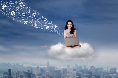 Beautiful teenage girl typing on laptop computer while sitting on the cloud at sky photo