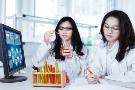 estudiantes medicina: Colegialas adolescentes hermosa que hace el experimento con el líquido químico en el laboratorio
