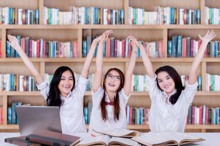 teenagers school: Happy high school students studying in the library and raise hands together