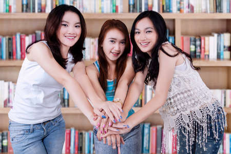 Portrait of beautiful female students standing in the library while joining their hands photo