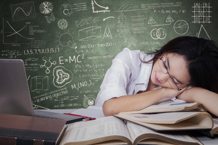 textbooks: Beautiful teenage schoolgirl sleeping on desk over textbooks and looks tired after studying