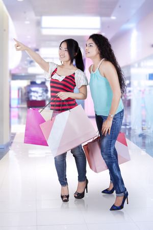 spending full: Pretty asian girls holding shopping bags while looking at a store together, shot in the shopping center Stock Photo