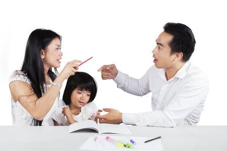 pareja enojada: Dos padres asiáticos que discuten juntos cuando ayuda a su hija a estudiar