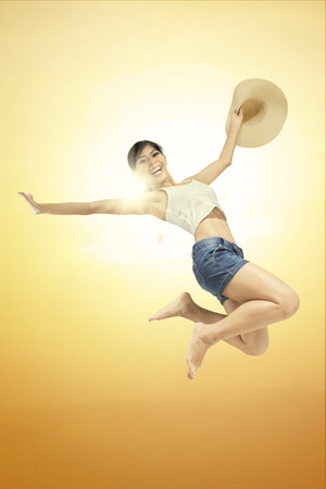 summer wear: Happy woman wears summer wear and holds a hat, jumping under beautiful sunset