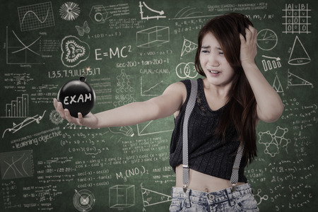 examination stress: Portrait of nervous female student standing in the class while holding a bomb with an exam text Stock Photo