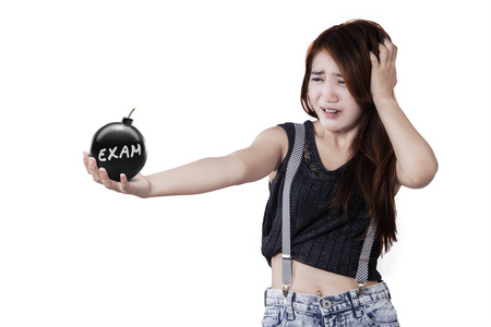 Fear female student holding a bomb with an exam text, isolated on white background Stock Photo