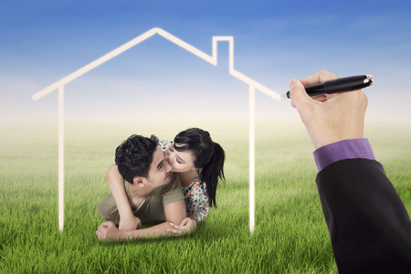 dream house: Portrait of happy couple kissing on the meadow under a dream home Stock Photo