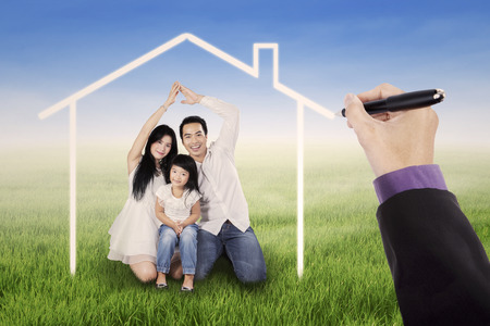 dream vision: Beautiful family sitting on the meadow under a dream home, shot outdoors