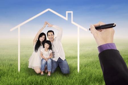 Hermosa familia sentado en el prado bajo una casa de ensueño, disparó al aire libre